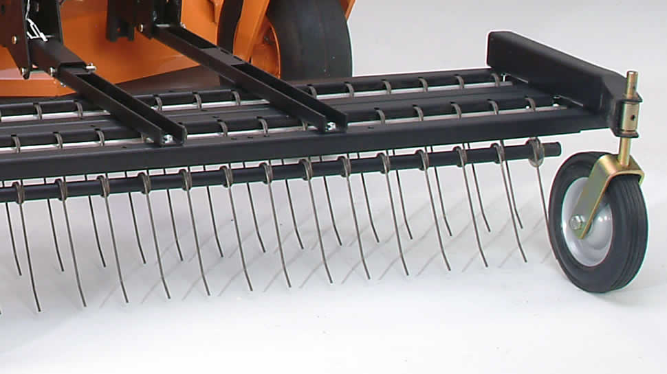 The stabilizer tube through the lower loop of tines maintains tine spacing, allowing zero-turns without lifting the rake or damaging the turf.