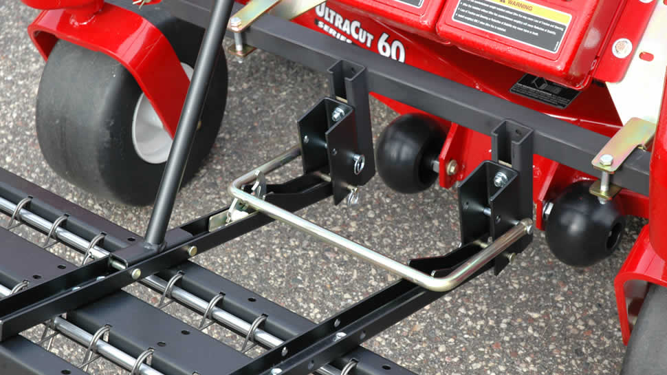 The Tine Rake Dethatcher attaches to the JRCO mount system with clevis pins. A heavy duty latch bar secures both arms.