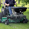 Action shot of Jrco broadcast spreader mounted to a zero turn mower