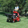 Action shot of Jrco broadcast spreader mounted to a stand-on mower