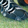 "Close up action shot of Jrco 38"" front-mount hooker aerator mounted to a zero turn mower"