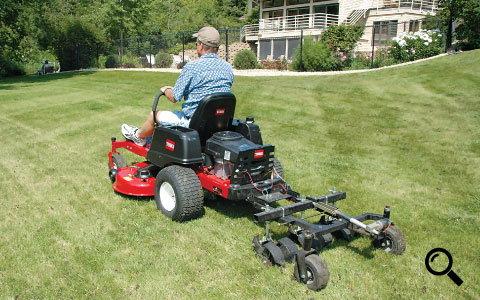 "Action shot of Jrco 38"" tow-behind hooker aerator mounted to a zero turn mower"